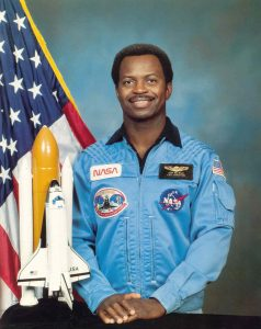 A formal NASA portrait of Ronald E. McNair, he proudly stands in front of a model of the shuttle, Challenger